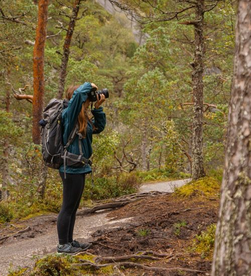 Chica tomando fotografias por el sendero del valle de Husedalen