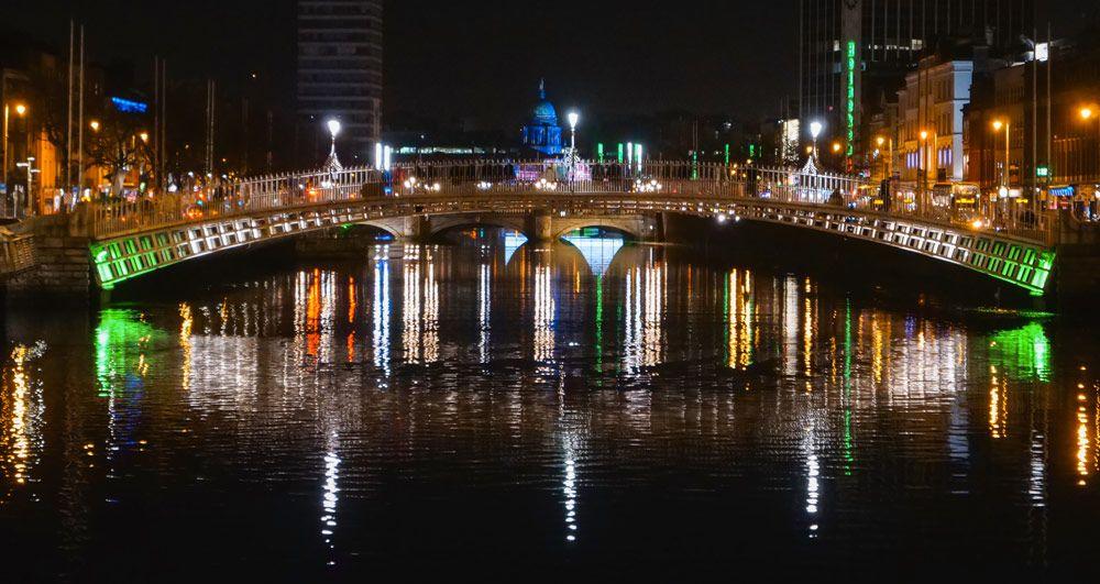 los puentes de dublín iluminados con su reflejo en el agua