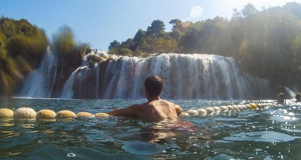 Chico bañándose casi debajo de la catarata Skradin Buk del Parque Nacional Krka