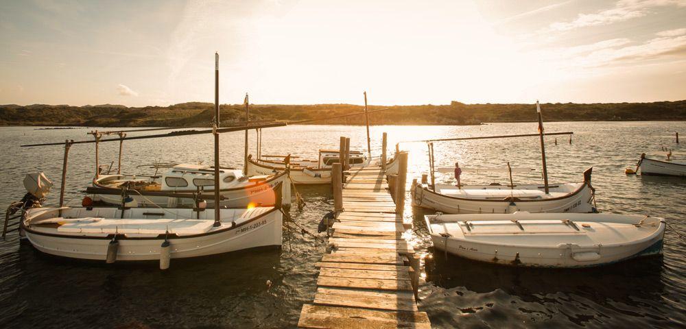 barcas en un puerto de madera cercano a Far de Cavalleria