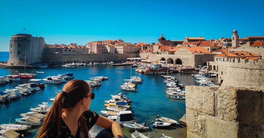 Chica observando las barcas del puerto viejo del casco antiguo de la Perla del Adriático