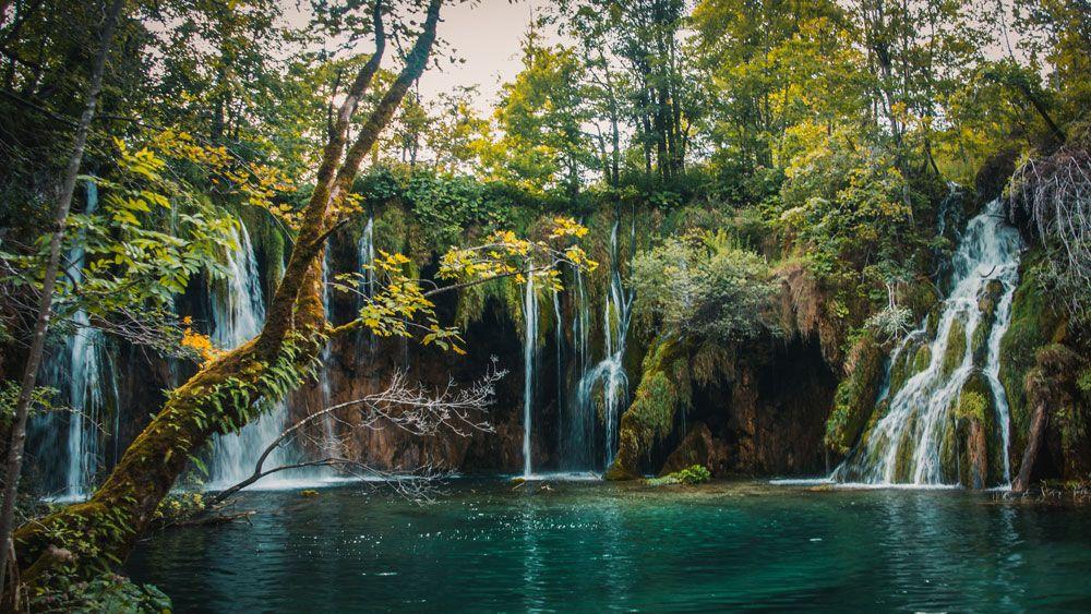 Lago de agua turquesa con varios saltos de agua a su alrededor en el parque nacional de lagos de Pltivice