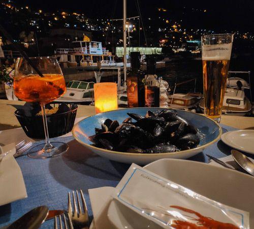 Mejillones y bebida en un restaurante en el puerto viejo de Dubrovnik