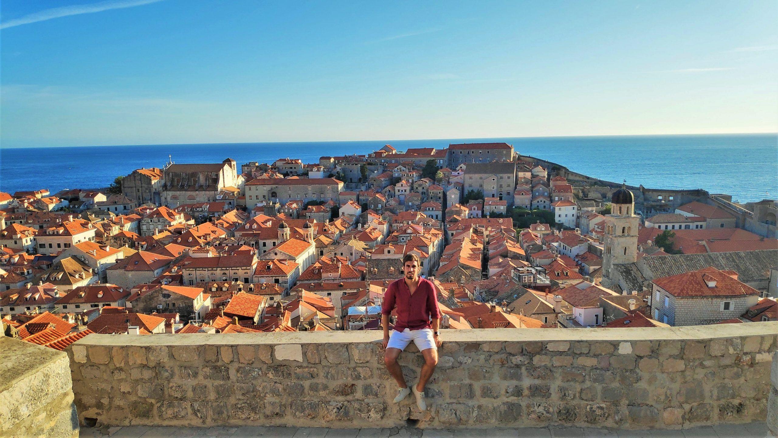 Chico sentado en un muro con la ciudad de Dubrovnik a su espalda