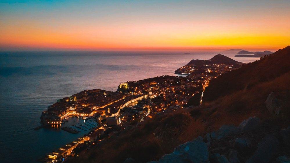 Increíble puesta de sol des de lo alto de la montaña de Dubrovnik con la ciudad de fondo al lado del mar