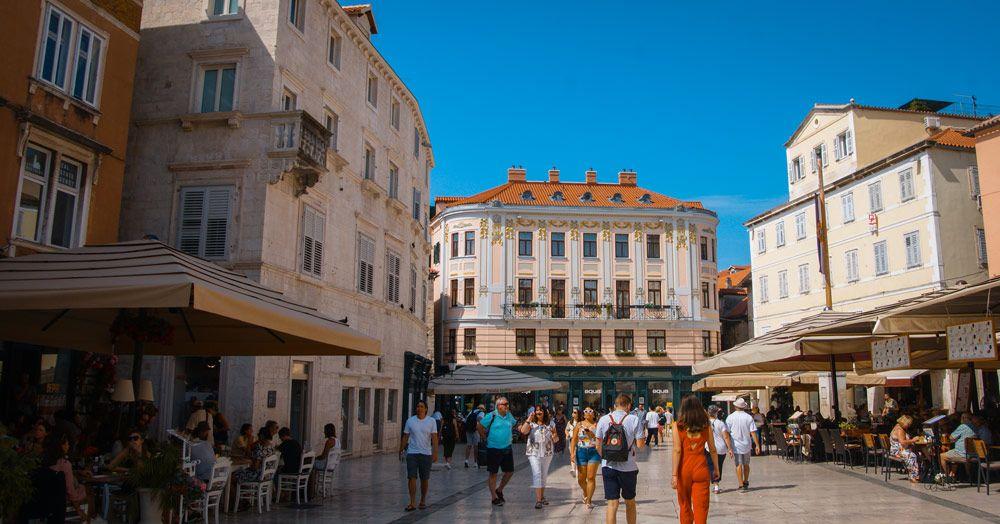 Plaza con gente paseando y con un edificio clásico en el fondo en Split